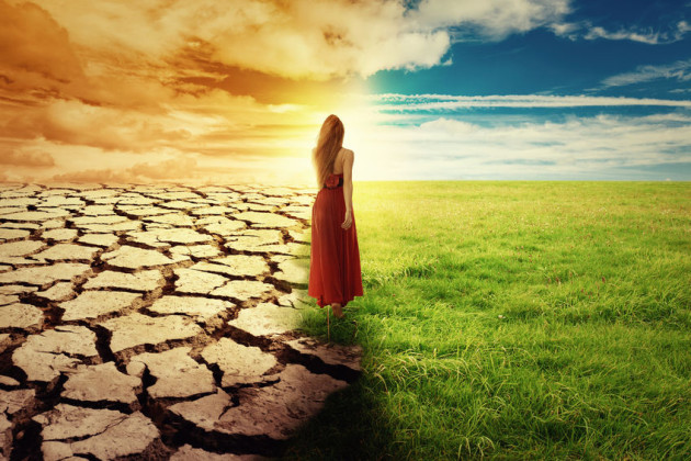 37959342 - a climate change concept image. landscape of a green grass and drought land. woman in green dress walking through an opened field